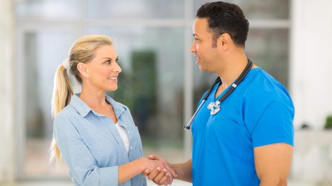 caring medical doctor greeting senior patient